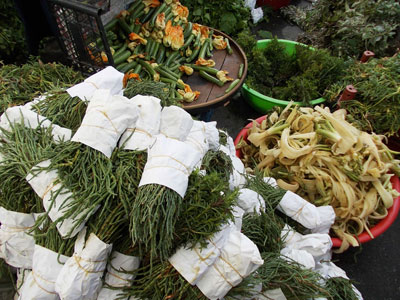 Deniz börülcesi (samphire, foreground) and şevketibostan (milk  thistle, center) for sale in the Alaçatı market, photo by Jennifer Hattam